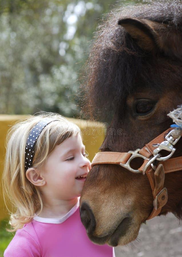 La petite fille blonde aime sa verticale drôle d'âne photos libres de droits
