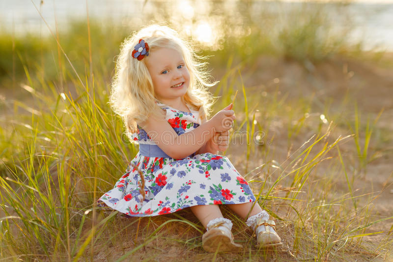La petite fille blonde bouclée s'assied et sourit sur le sable et l'herbe au su photographie stock