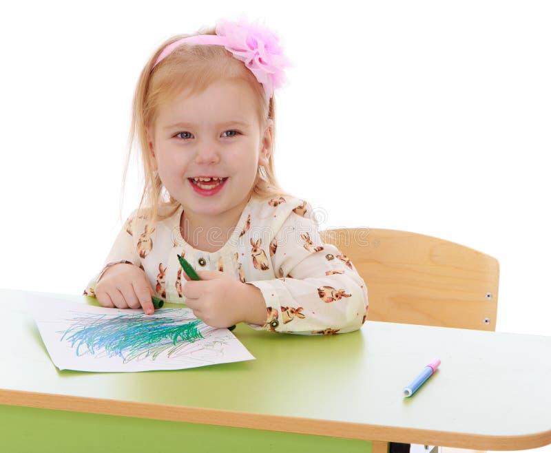 La petite fille blonde caucasienne dessine avec des crayons image libre de droits