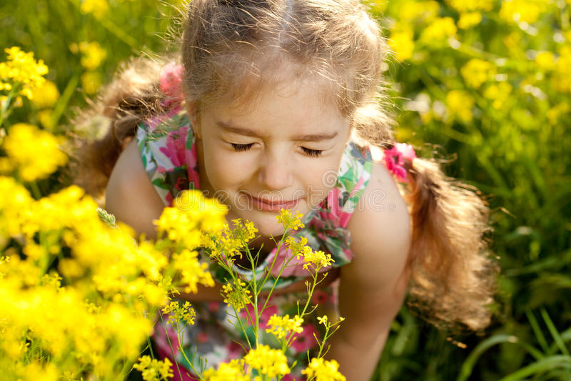 La petite fille blonde inhale le parfum des fleurs photo stock