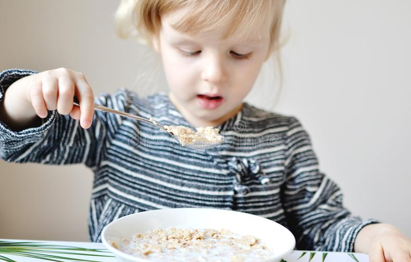 La petite fille blonde mangeant le petit déjeuner sain s'écaille avec du lait photos libres de droits