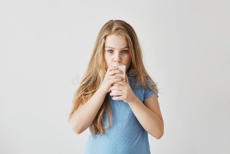 La petite fille blonde mignonne avec les yeux bleus avec du charme a concentré regarder l'appareil-photo et le verre à boire de l image libre de droits