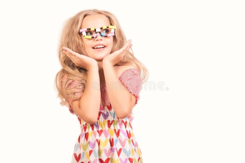 La petite fille blonde mignonne dans la robe avec des coeurs et des verres recherche la bouche latérale d'ouverture dans la surpr images stock