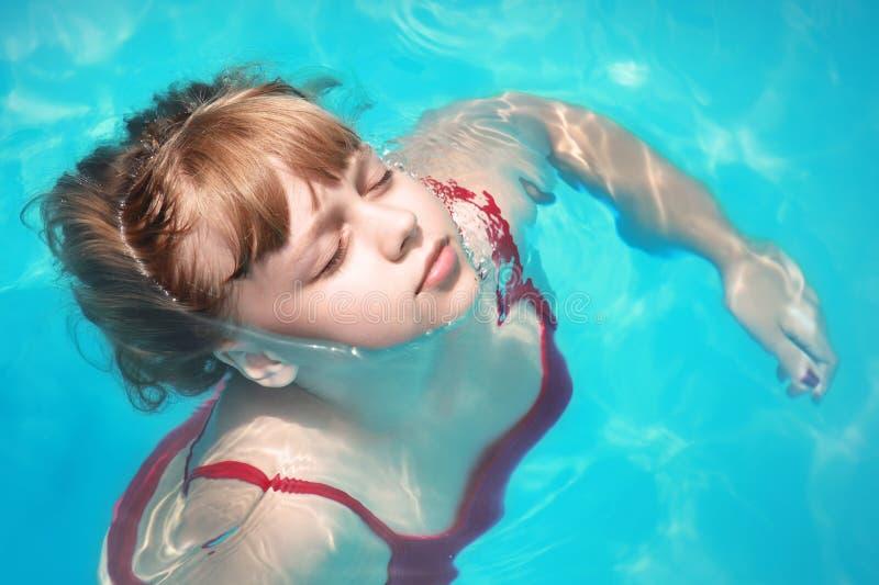 La petite fille blonde nage décontracté avec les yeux fermés photo libre de droits