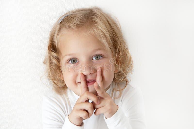 La petite fille blonde a rectifié dans le blanc photos stock