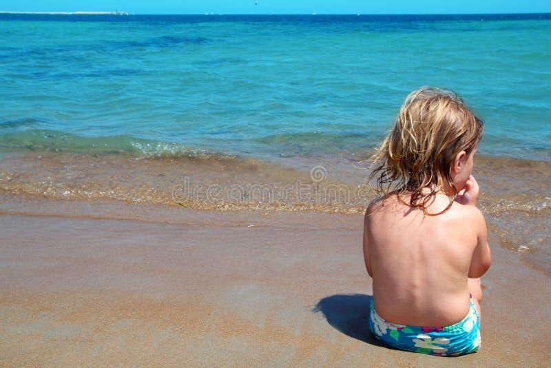 La petite fille blonde s'asseyent dans le rivage de plage regardant l'océan photos libres de droits