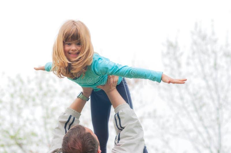 La petite fille blonde s'est soulevée haut dans le ciel par son père extérieur images stock
