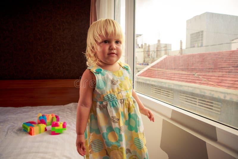 la petite fille blonde se tient prêt la côté-vue de fenêtre image libre de droits