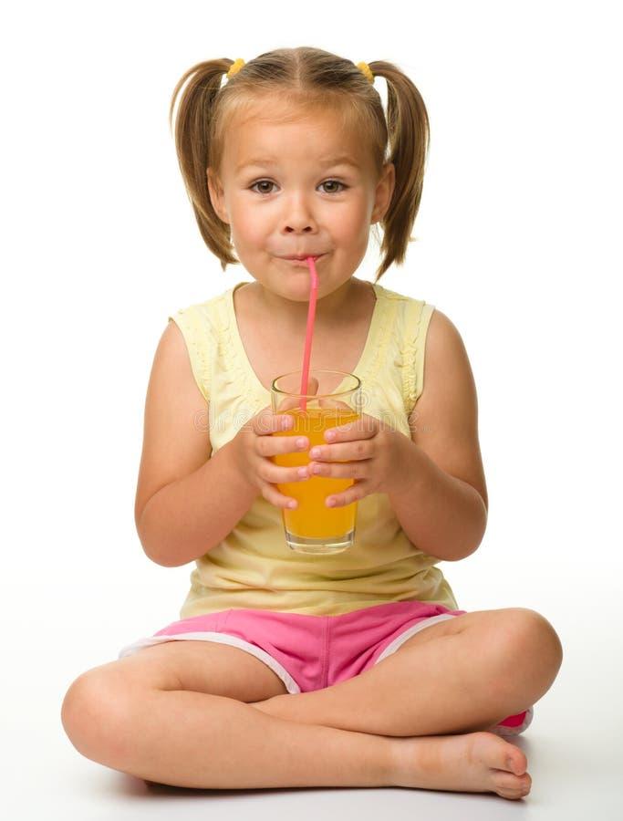 La petite fille boit du jus d'orange photos libres de droits