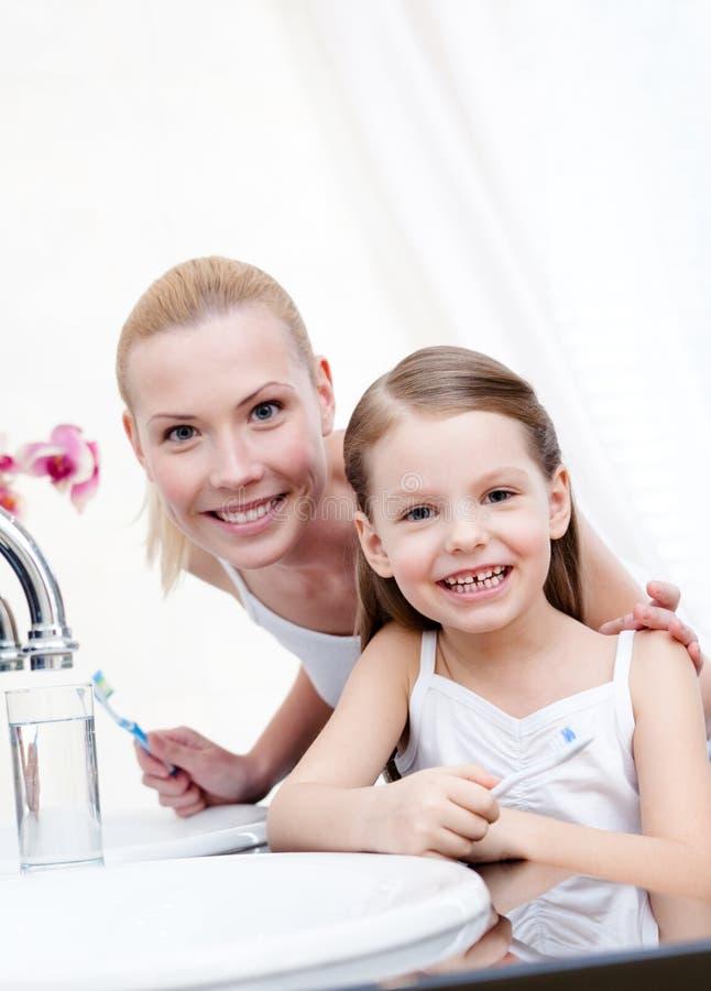 La petite fille brosse des dents avec sa momie photographie stock