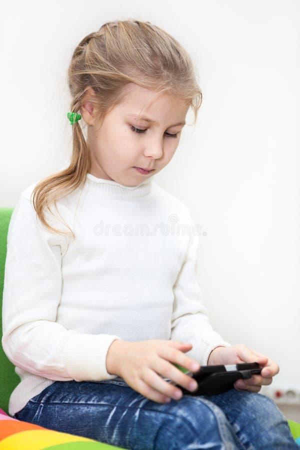 La petite fille caucasienne a accès net illimité Utilisation d'Internet avec le smartphone photo libre de droits