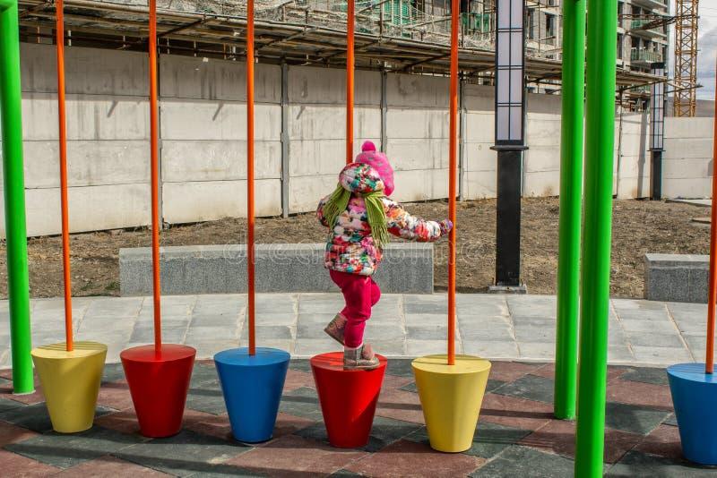 La petite fille, chaudement habillée, dans des jeux d'un chapeau et de veste sur le terrain de jeu avec des glissières et des osc photo stock