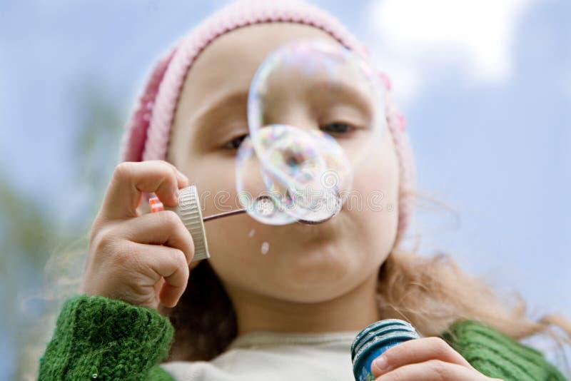 La petite fille commence vers le haut des bulles de savon images libres de droits