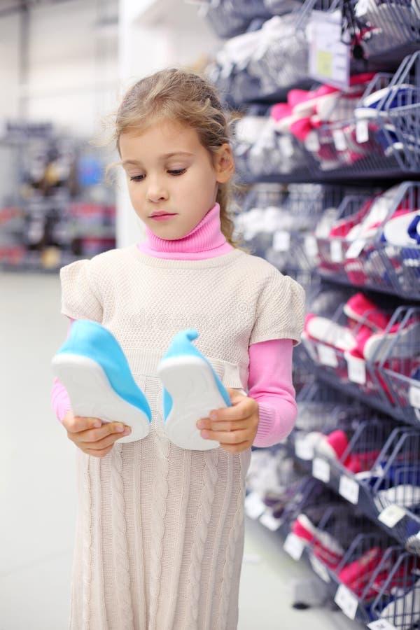 La petite fille considère des chaussures de gymnase et reste les étagères proches photos libres de droits