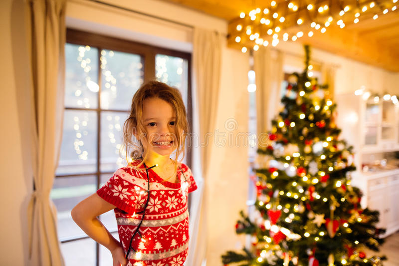 La petite fille décorant l'arbre de Noël a embrouillé dans les lumières à chaînes images stock