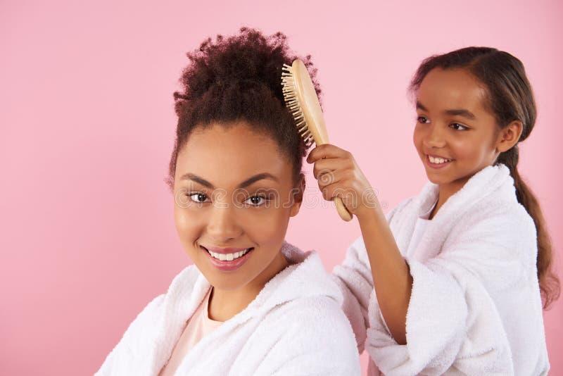 La petite fille d'Afro-américain peigne la mère images libres de droits