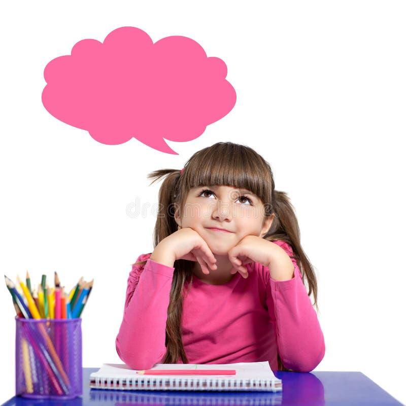 La petite fille d'isolement dans une chemise rose s'assied à l'esprit de table photo stock