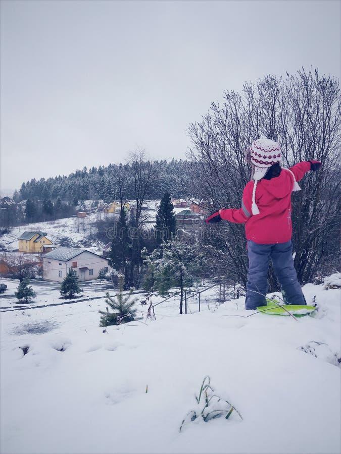 La petite fille dans des vêtements d'hiver pour la vue arrière de sport, regarde image stock