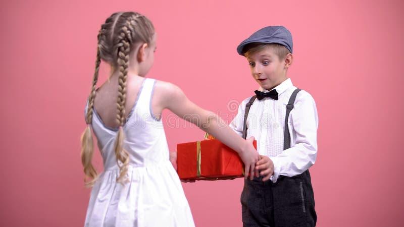 La petite fille dans donner blanc de robe a enveloppé actuel à l'ami, jour de valentines photos stock