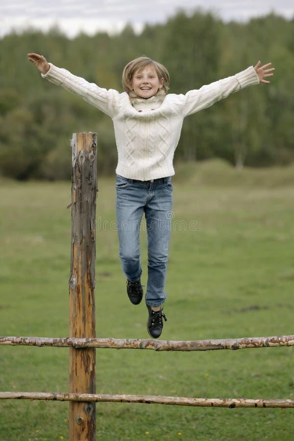 La petite fille dans le chandail et des blues-jean blancs saute outre de la barrière Portrait de mode de vie photo stock