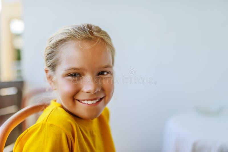 La petite fille dans le chemisier jaune s'assied sur une chaise photo libre de droits