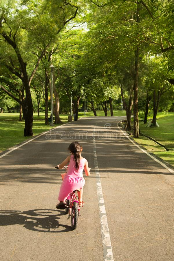 La petite fille dans la robe rose essayant de monter un vélo s'est dirigée pour une rue étroite dans le parc photographie stock libre de droits
