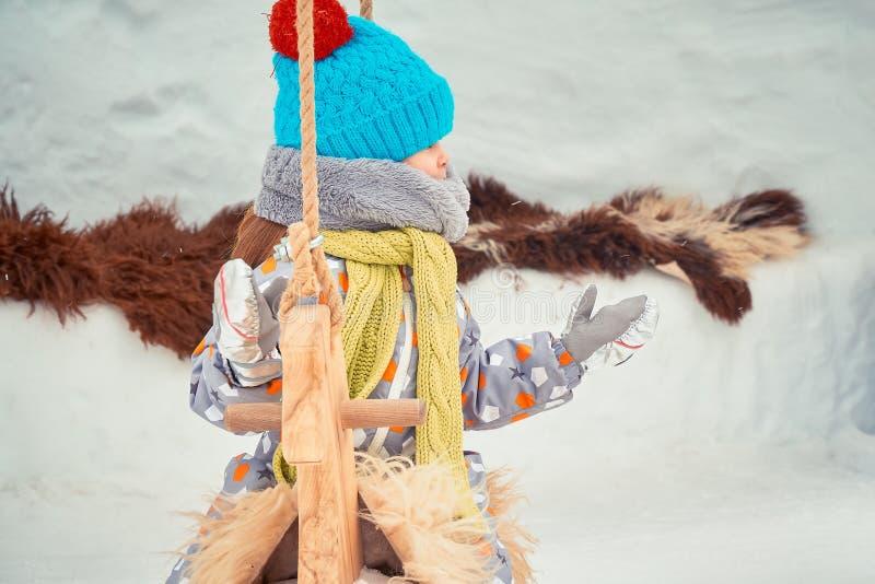La petite fille dans un chapeau et une écharpe joue sur le carrousel photos stock