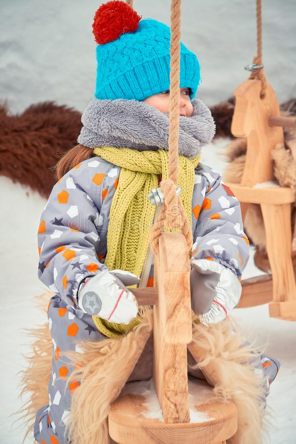 La petite fille dans un chapeau et une écharpe joue sur le carrousel photographie stock