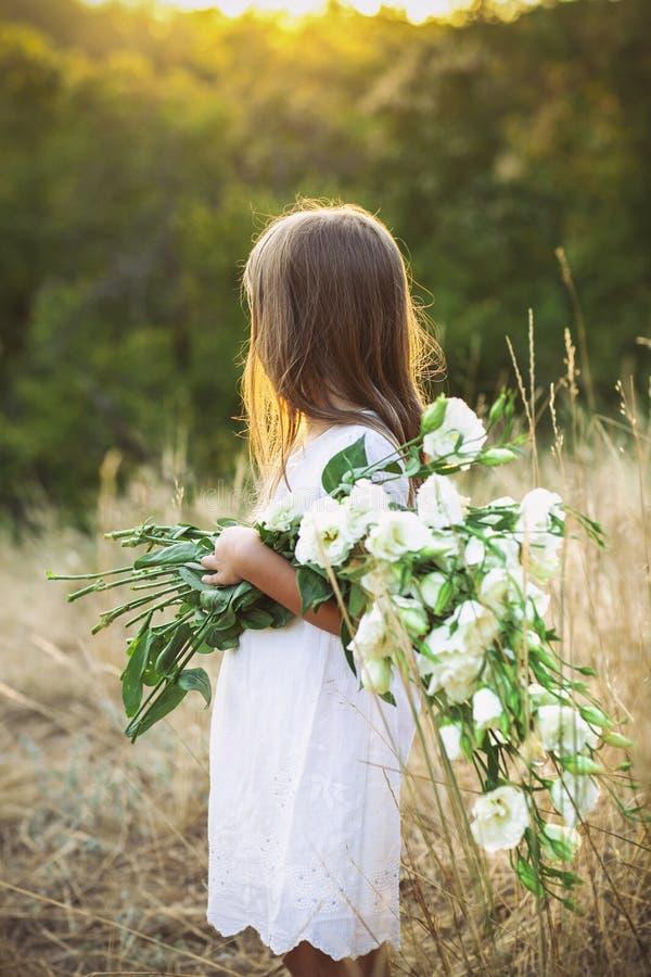 La petite fille dans un pré avec l'été sauvage blanc fleurit photos stock