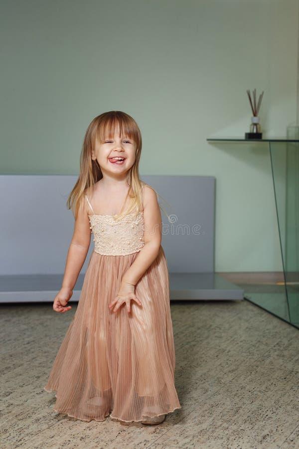 La petite fille dans une belle robe joue à la maison photos libres de droits