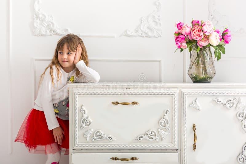 La petite fille dans une jupe rouge s'est penchée sur la raboteuse Sur la raboteuse est un bouquet des tulipes photographie stock libre de droits