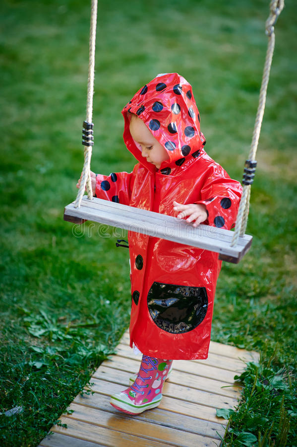La petite fille dans une veste rouge se tient près de l'oscillation photo libre de droits