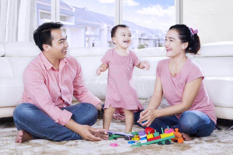 La petite fille danse avec ses parents à la maison photographie stock libre de droits