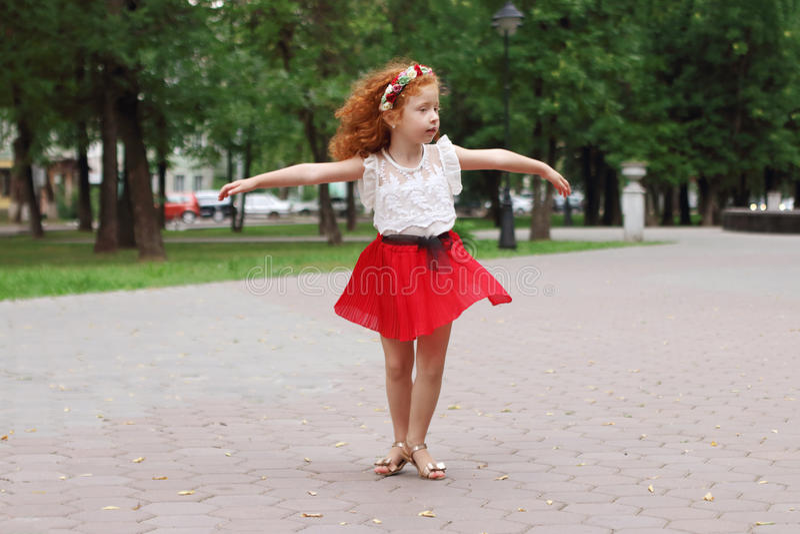 La petite fille danse en parc vert d'été, d peu profond photos stock