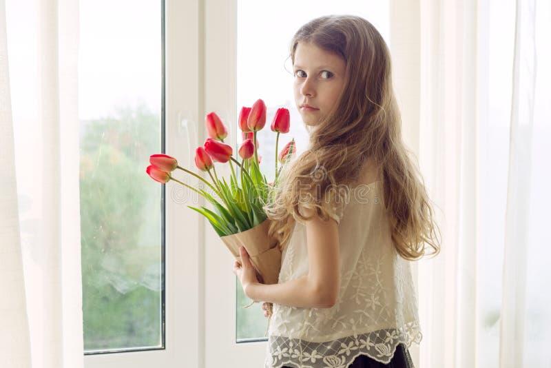 La petite fille de bel enfant avec le bouquet des fleurs rouges de tulipes à la maison près de la fenêtre, se présentent pour la  images libres de droits