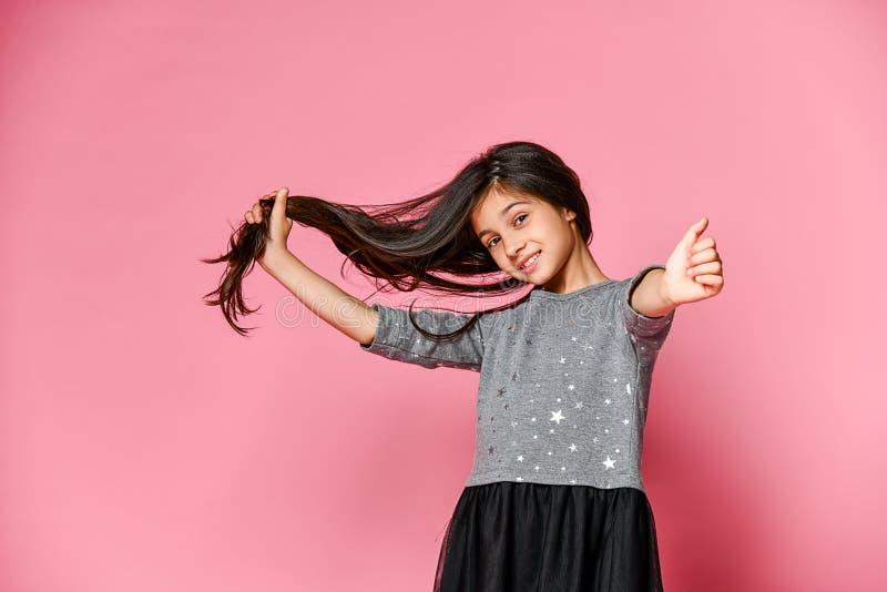 La petite fille de brune avec de longs cheveux tient une mèche de ses cheveux et montre la classe avec son pouce Quels longs chev images libres de droits