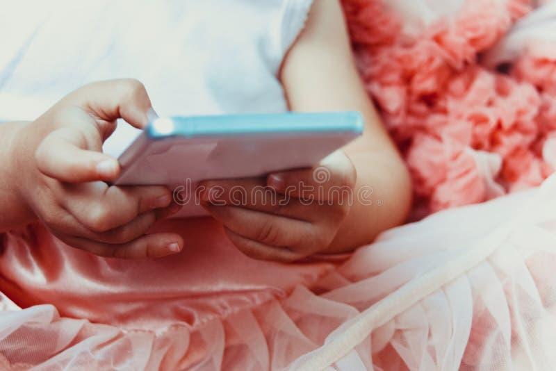 La petite fille de petite fille dans une belle jupe rose pelucheuse avec des ruches utilisent le téléphone portable blanc image libre de droits