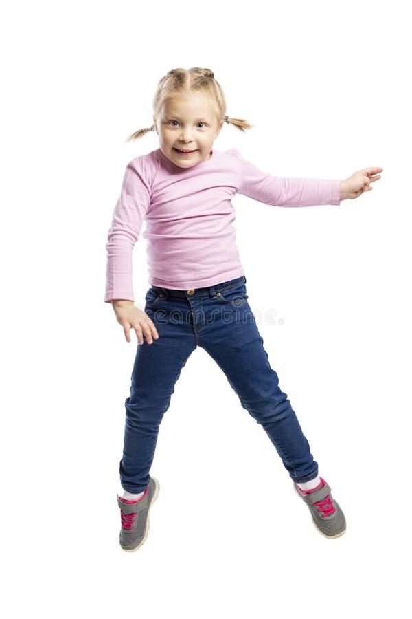 La petite fille de l'âge préscolaire dans un chandail rose et des jeans saute D'isolement au-dessus du fond blanc photos libres de droits