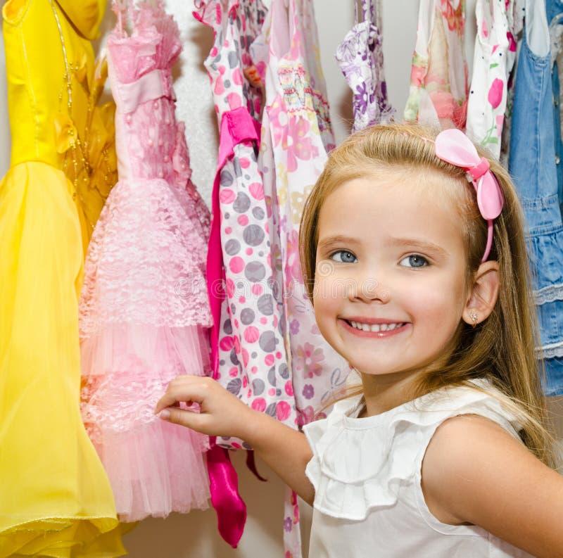 La petite fille de sourire choisit une robe de la garde-robe images libres de droits