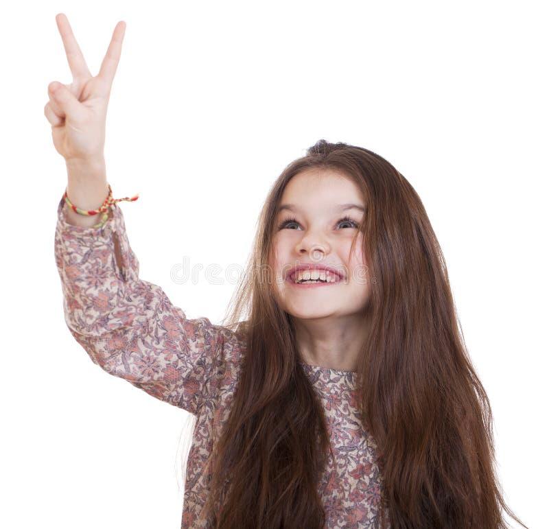 La petite fille de sourire dans la robe montrant la paix font des gestes avec des doigts images libres de droits