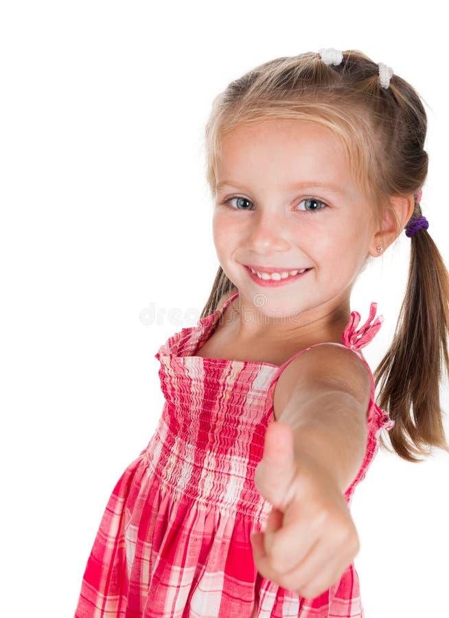 La petite fille de sourire fait le pouce  photo stock