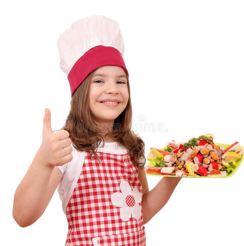 La petite fille de sourire font cuire avec les fruits de mer et le pouce  images libres de droits