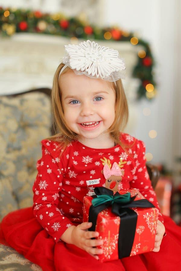 La petite fille de sourire portant la robe rouge, gardant le cadeau et s'asseyant sur le sofa près a décoré la cheminée image stock