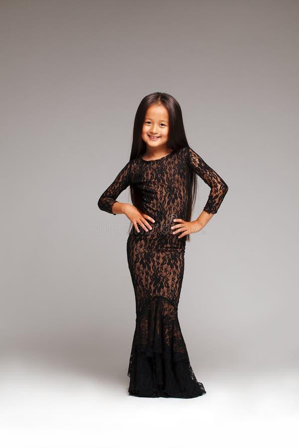 La petite fille de sourire posant dans la dentelle noire s'habillent photos stock