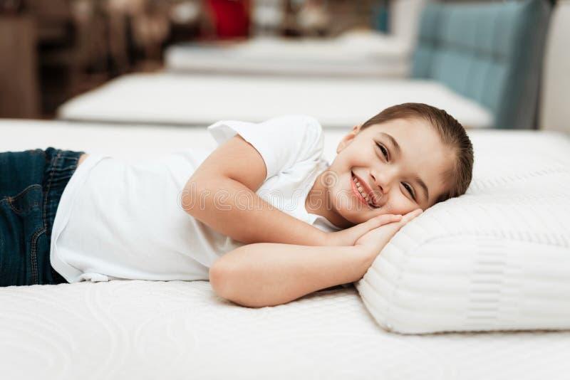 La petite fille de sourire se trouve sur le matelas orthopédique de n dans un magasin de meubles photo stock
