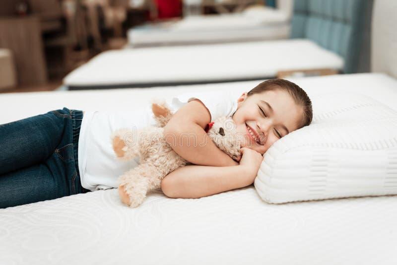 La petite fille de sourire se trouve sur le matelas orthopédique de n dans un magasin de meubles photographie stock libre de droits