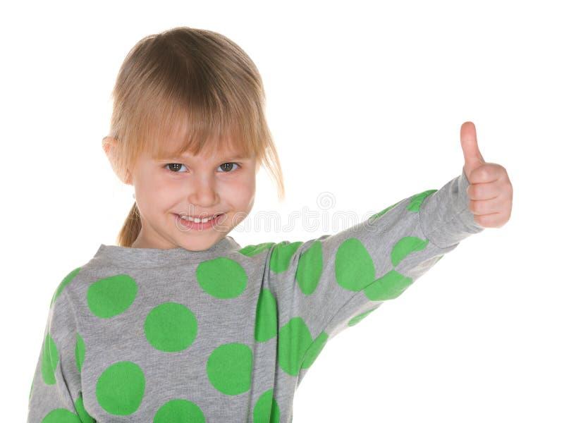 La petite fille de sourire tient le pouce  photo stock
