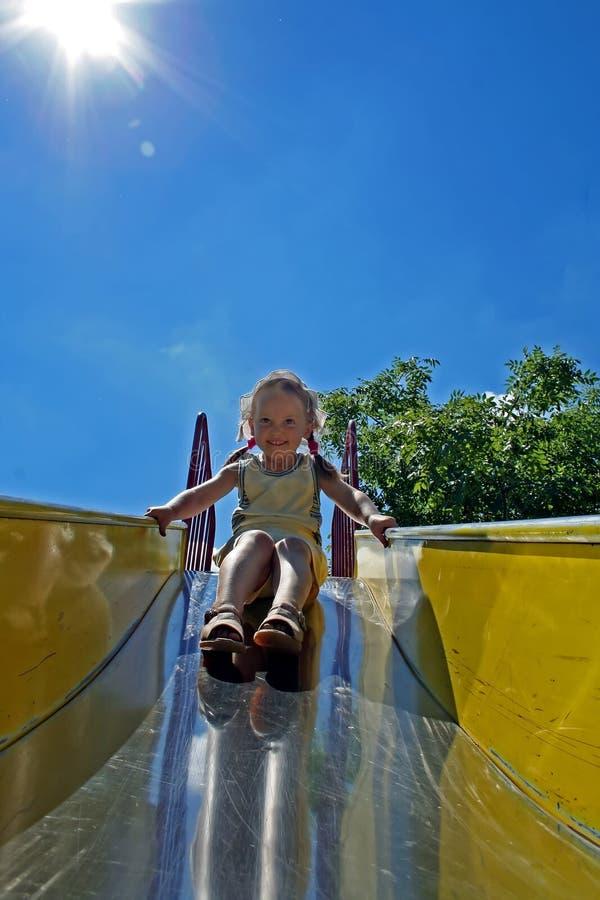 la petite fille de sourire va chercher une commande sur un children& x27 ; colline de s image libre de droits