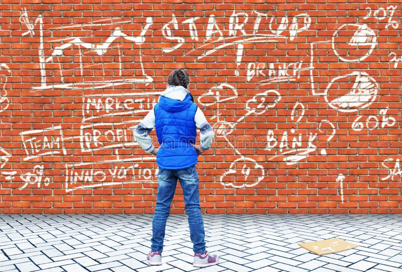 La petite fille a dessiné avec la craie sur un mur de briques le dessin d'un démarrage d'entreprise photo libre de droits