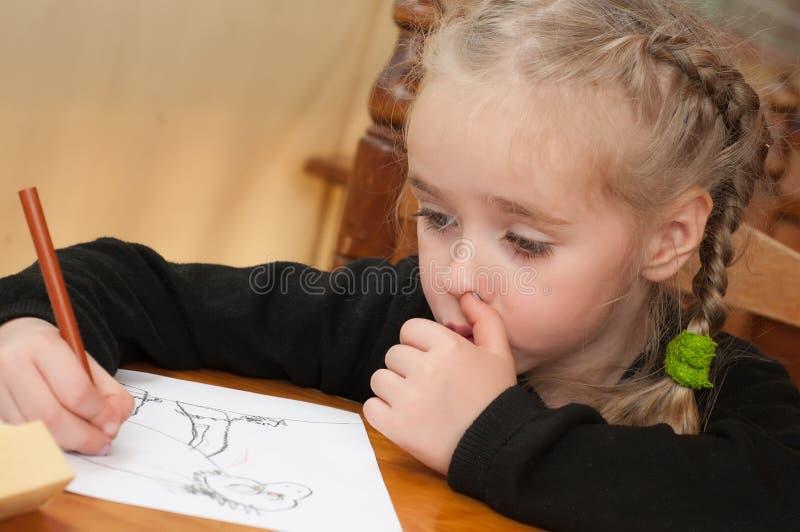 La petite fille dessine image stock